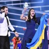 Ukraine's Jamala celebrates after receiving the trophy from co-host and 2015 Eurovision winner Mans Zelmerlow after winning the Eurovision Song Contest final with the song '1944' in Stockholm, Sweden, Sunday, May 15, 2016. (ANSA/AP Photo/Martin Meissner)