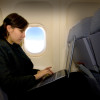 Business woman using laptop during the flight