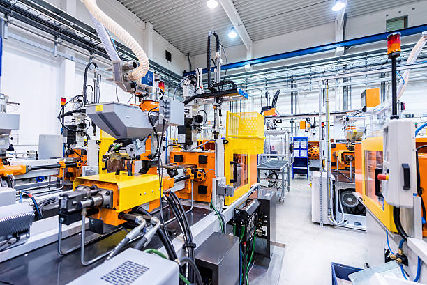 Horizontal color image of large group of automated injection moulding machines for plastic parts production.